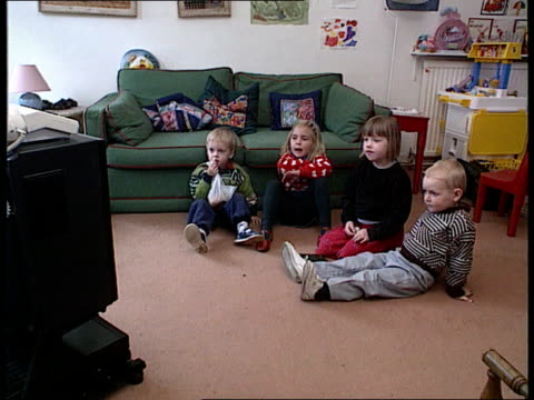 parents responsibility; england london tms four small children sitting on floor watching television cms little boy and girl ditto - bericht film und fernsehen stock-videos und b-roll-filmmaterial