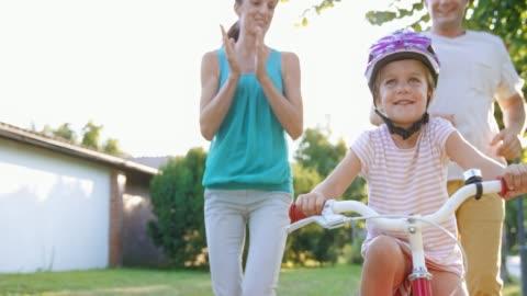 vídeos y material grabado en eventos de stock de slo mo ds padres corriendo junto a su chica en su bicicleta por primera vez y aplaudiendo - 40 44 años