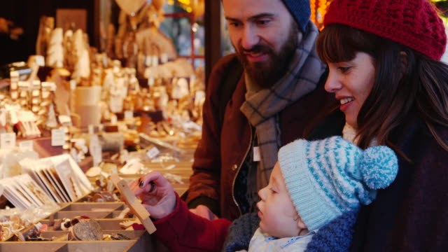 parents show young child ornaments at christmas market stall. - お土産点の映像素材/bロール