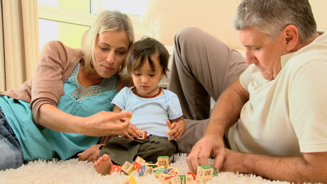 parents showing different colored blocks to their baby on carpet / cape town, western cape, south africa - 横向きに寝る点の映像素材/bロール