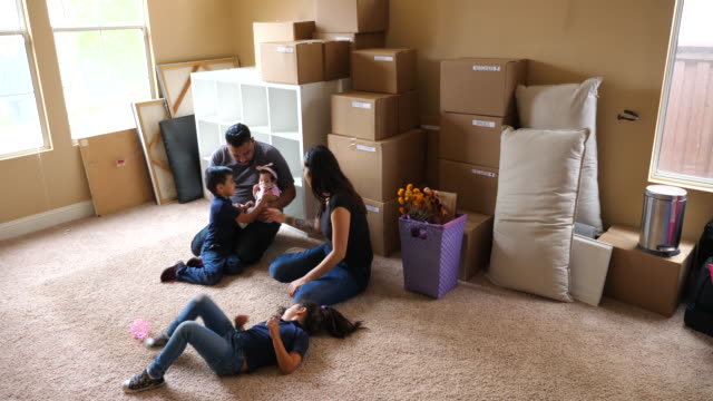 ms parents sitting with young children on floor of living room of new home during move in day - latin american and hispanic ethnicity stock videos & royalty-free footage