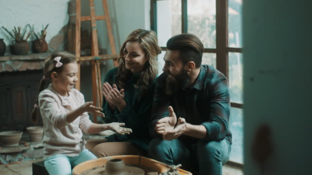 陶器の作り方を学ぶ親記述娘 - 陶芸家点の映像素材/bロール