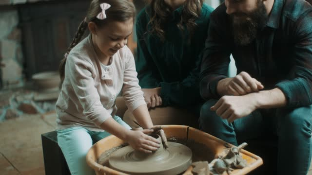 parents suporting daughter to learn how to make pottery - potter stock videos and b-roll footage