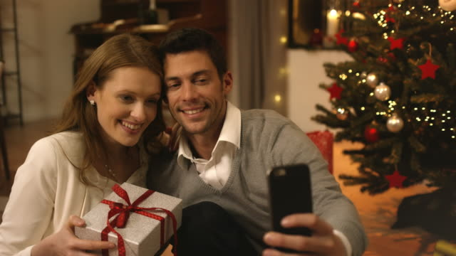 parents taking selfies on christmas eve - christmas present stock videos and b-roll footage