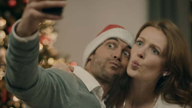 parents taking selfies on christmas - couple relationship photos stock videos & royalty-free footage
