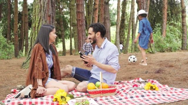 stockvideo's en b-roll-footage met ouders praten op een picknick terwijl de kinderen spelen - picnic