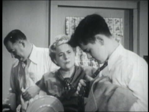 B/W 1949 parents talking to teenage boy as he puts on tie / they laugh + shake their heads as exits