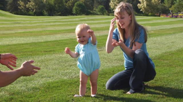 slo mo ms parents teaching daughter (6-11 months) to walk / utah, usa - erste schritte stock-videos und b-roll-filmmaterial