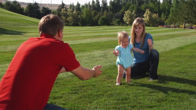 vidéos et rushes de slo mo ws parents teaching daughter (6-11 months) to walk / utah, usa - pelouse