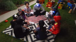 Parents telling scary stories to kids at outdoor Halloween party
