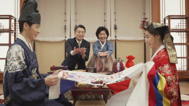 parents throwing jujubes to bride and groom during pyebaek (traditional ceremony of korea after wedding) - korean ethnicity stock videos & royalty-free footage