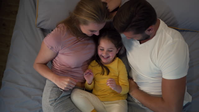 parents tickling their little daughter while relaxing in the living room - tickling stock videos & royalty-free footage