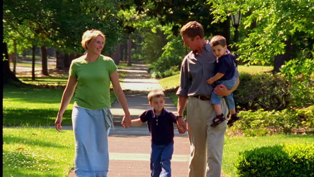 vidéos et rushes de parents walk with their young sons in their suburban neighborhood. - trottoir
