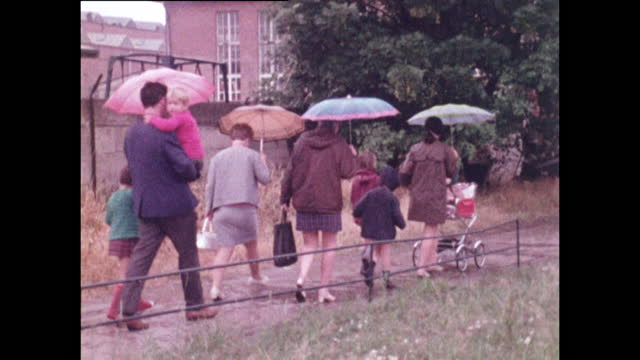 ws parents walking home with children and pushchairs in rain; 1970 - germany stock videos & royalty-free footage