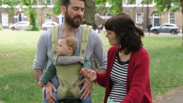 parents walking in city park, father carrying baby son in baby carrier. - sportkinderwagen stock-videos und b-roll-filmmaterial