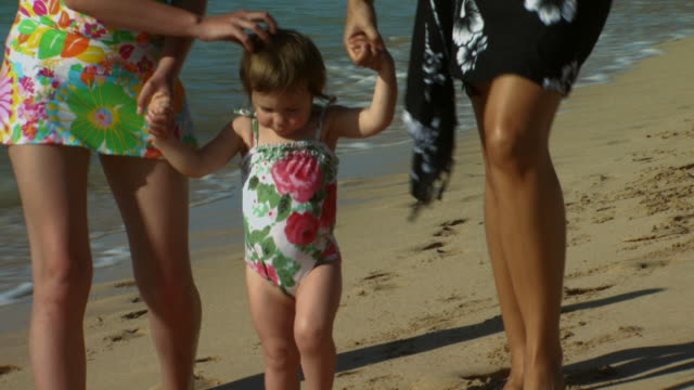 parents walking on beach with daughter holding hands - see other clips from this shoot 1141 stock videos & royalty-free footage