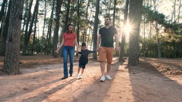 vídeos y material grabado en eventos de stock de padres caminando con un hijo mayor en el bosque de pinos durante la puesta de sol - son