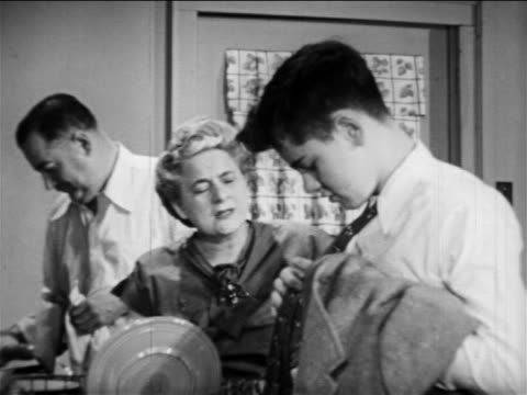 B/W 1949 parents washing + drying dishes talking to son adjusting tie in kitchen / educational