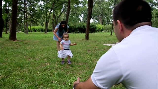 vídeos de stock, filmes e b-roll de pais assistindo bebê filha dar primeiros passos - primeiros passos