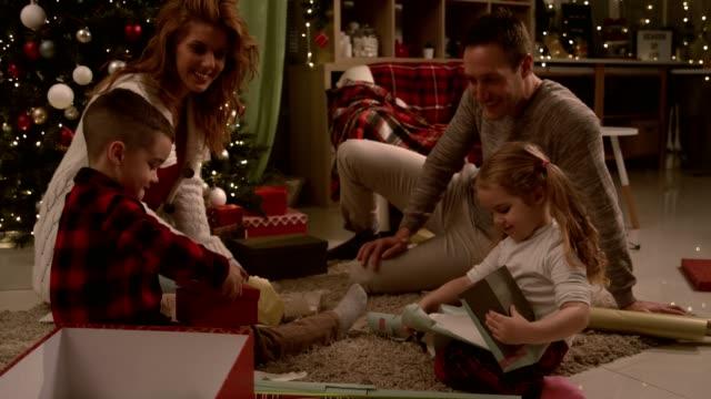 vidéos et rushes de les parents regardant leurs deux adorables enfants ouvrent leurs cadeaux de noel - cadeau de noël