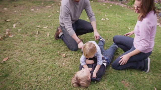 vidéos et rushes de parents watching their two boys wrestling on the grass - jouer à la bagarre