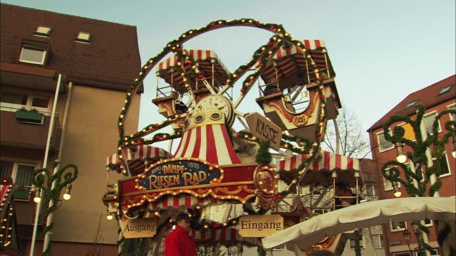 ws td tu parents waving to children riding small ferris wheel at christmas market (kinderweihnacht) / nuremberg, bavaria, germany - nuremberg stock videos & royalty-free footage