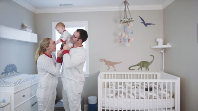vidéos et rushes de parents wearing matching pajamas with their 6 month old  caucasian baby boy in the baby nursery - pyjama