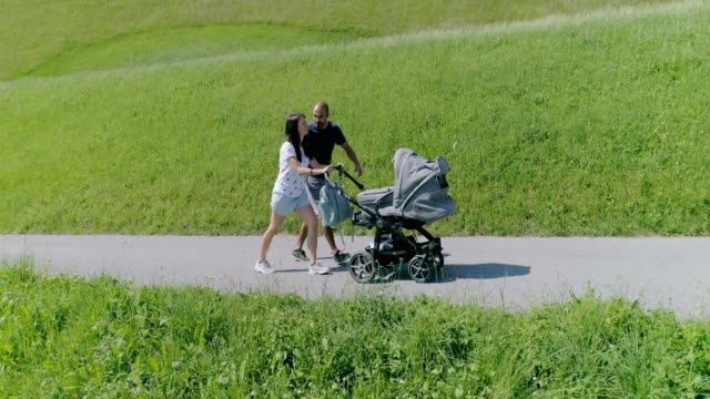 eltern mit baby in natur-slow-motion - sportkinderwagen stock-videos und b-roll-filmmaterial