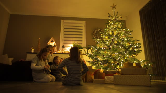 parents with children at christmas tree - family tree stock videos and b-roll footage