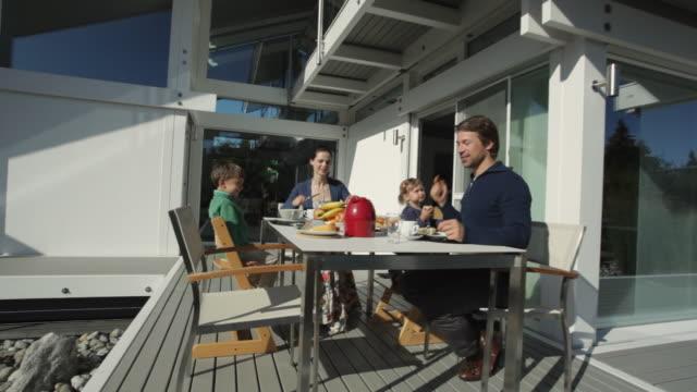 WS Parents with children (2-5) having breakfast on porch / Kleinmachnow, Brandenburg, Germany