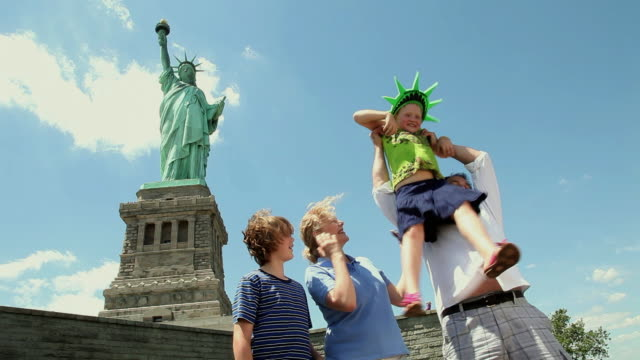 MS Parents with children (6-11) in front of statue of liberty, father picking girl / New York City, New York, USA