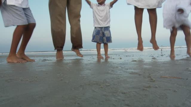 stockvideo's en b-roll-footage met ms zi slo mo parents with children (2-9) jumping on beach / jacksonville, florida, usa  - familie met drie kinderen