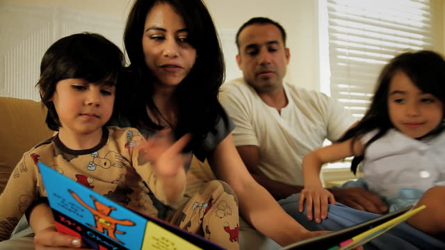 WS Parents with children on bed, mother and son (2-3) looking at picture book / Los Angeles, California, USA