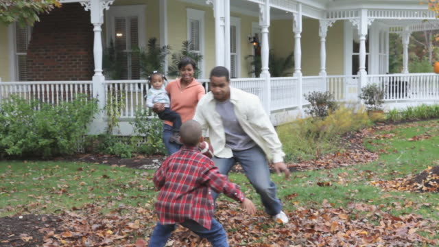 stockvideo's en b-roll-footage met ws pan parents with children (2-7) playing rugby ball together in front yard of home / richmond, virginia, usa. - voor of achtertuin