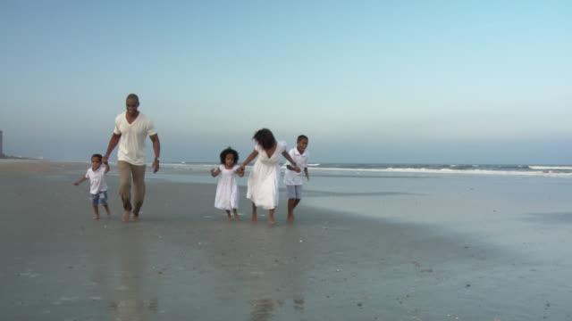 stockvideo's en b-roll-footage met ws slo mo parents with children (2-9) running on beach / jacksonville, florida, usa  - familie met drie kinderen