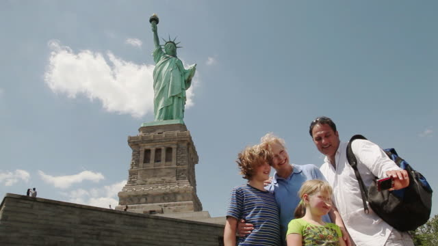 ms parents with children (6-11) taking self portrait in front of statue of liberty / new york city, new york, usa - famous place stock videos & royalty-free footage