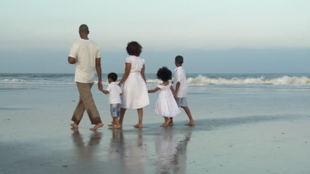 stockvideo's en b-roll-footage met ws pan parents with children (2-9) walking on beach / jacksonville, florida, usa - familie met drie kinderen