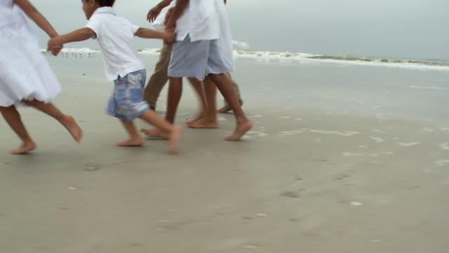 ms pov zi parents with children (2-9) walking on beach / jacksonville, florida, usa - familie mit drei kindern stock-videos und b-roll-filmmaterial