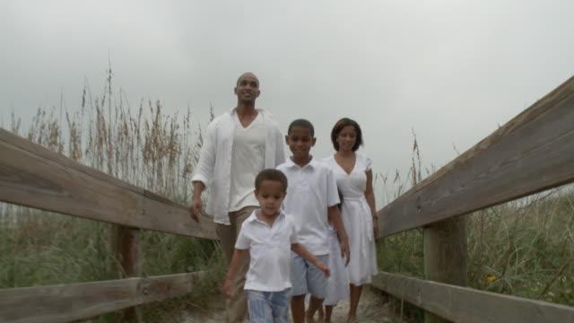ws pov parents with children (2-9) walking on beach walkway / jacksonville, florida, usa - familie mit drei kindern stock-videos und b-roll-filmmaterial