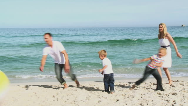 ws parents with daughter (8-9) and son (4-5) playing with ball on beach / cape town, south africa - ビーチボール点の映像素材/bロール
