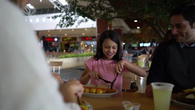 娘と一緒にモール内のフードコートで昼食を楽しんでいる親の話と笑顔