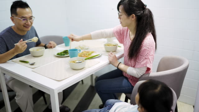 parents with daughter eating meal in the dining room - chinese food stock videos & royalty-free footage