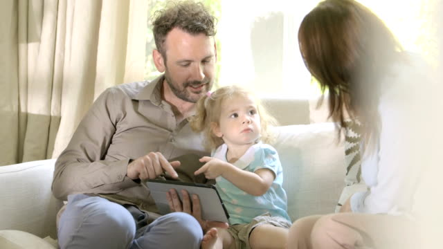 Parents with daughter on sofa with digital tablet.
