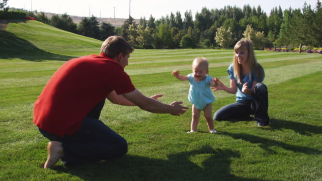 SLO MO WS Parents with daughter (6-11 months) relaxing on lawn / Utah, USA