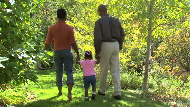 ws parents with daughter (18-23 months) walking in park / salt lake city, utah, usa - 18 23 months bildbanksvideor och videomaterial från bakom kulisserna
