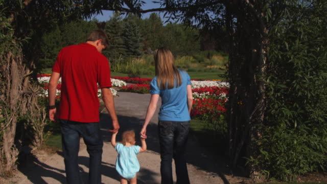 vídeos y material grabado en eventos de stock de slo mo ws td parents with daughter (6-11 months) walking in park / utah, usa - 6 11 months