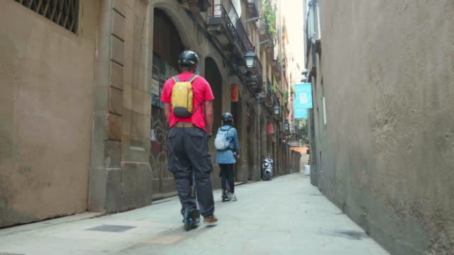 Parents with his childrens riding electric scooters in the narrow streets of Barcelona Born district during vacation