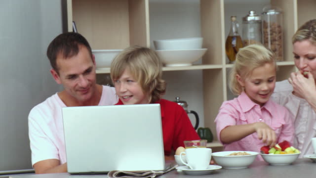 ms pan parents with son and daughter (8-9) eating breakfast and using laptop / cape town, south africa - see other clips from this shoot 1811 stock videos & royalty-free footage