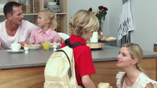 ms parents with son and daughter (8-9) in kitchen after breakfast / cape town, south africa - see other clips from this shoot 1811 stock videos & royalty-free footage