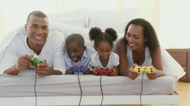 MS Parents with son and daughter (4-5) lying under sheets in bed and playing video games / Cape Town, Western Cape, South Africa